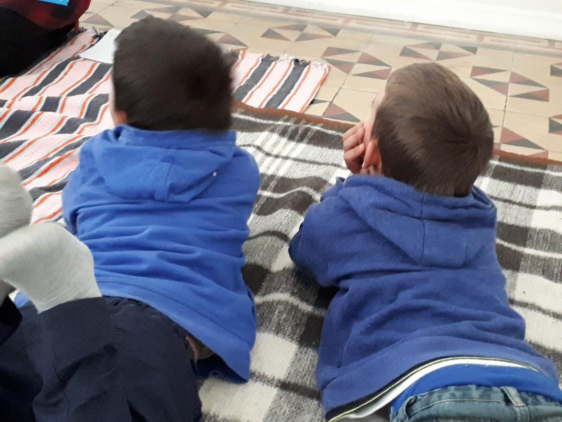 Duas crianças deitadas em cima de mantas no chão