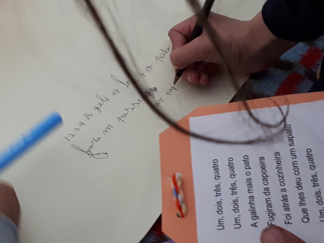 Criança a escrever em folha de papel