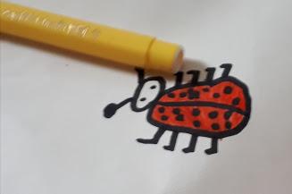 ponta de uma caneta amarela e desenho de uma joaninha