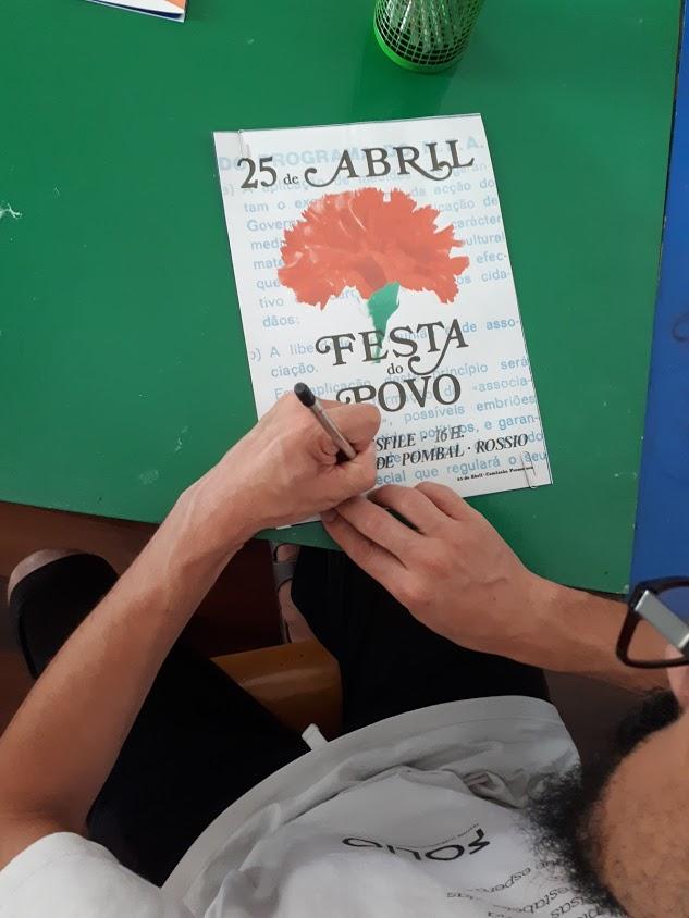 Adulto a desenhar um cravo num cartaz alusivo ao 25 de Abril