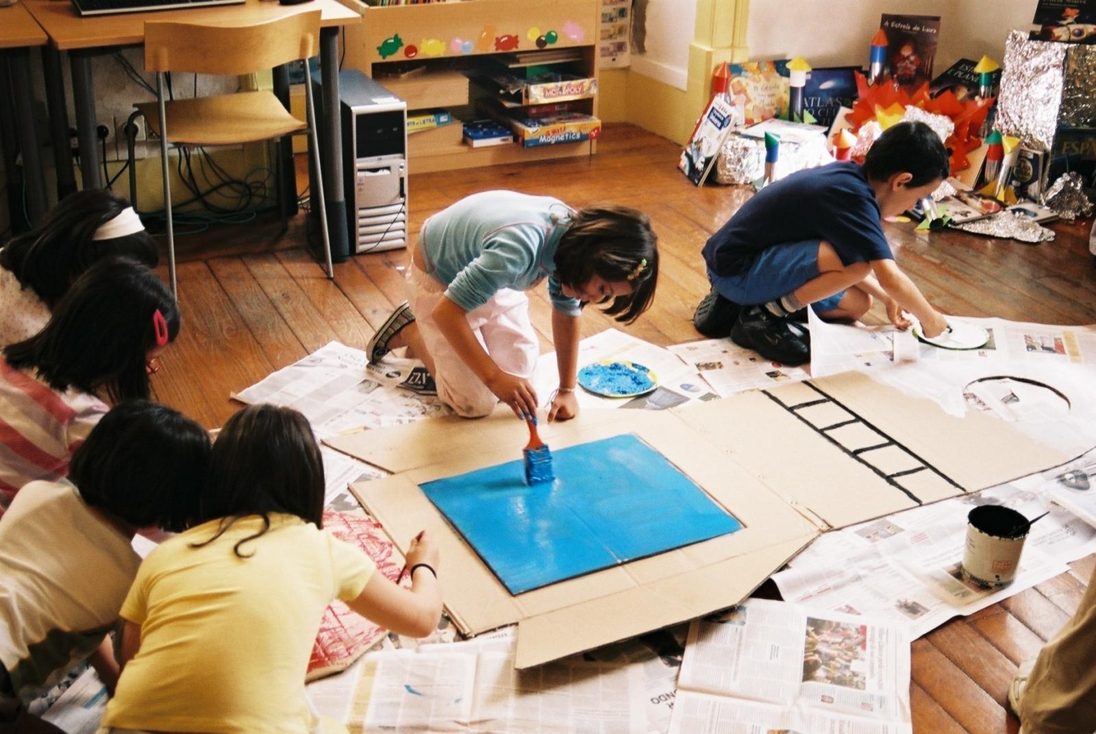 Grupo escolar adesenhar e pintar um foguetão no chão
