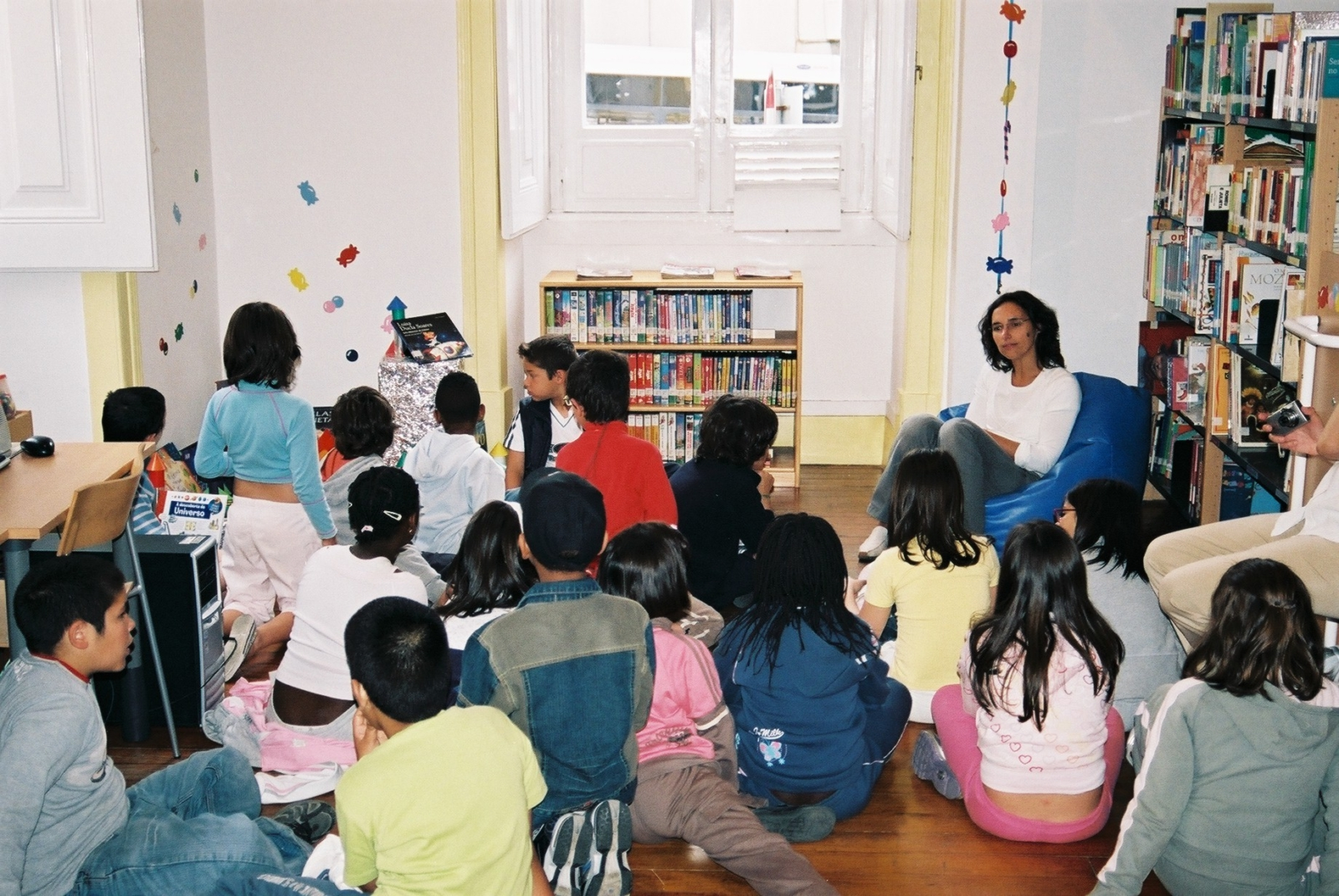 Grupo de crianças sentadas no chão a participar numa atividade