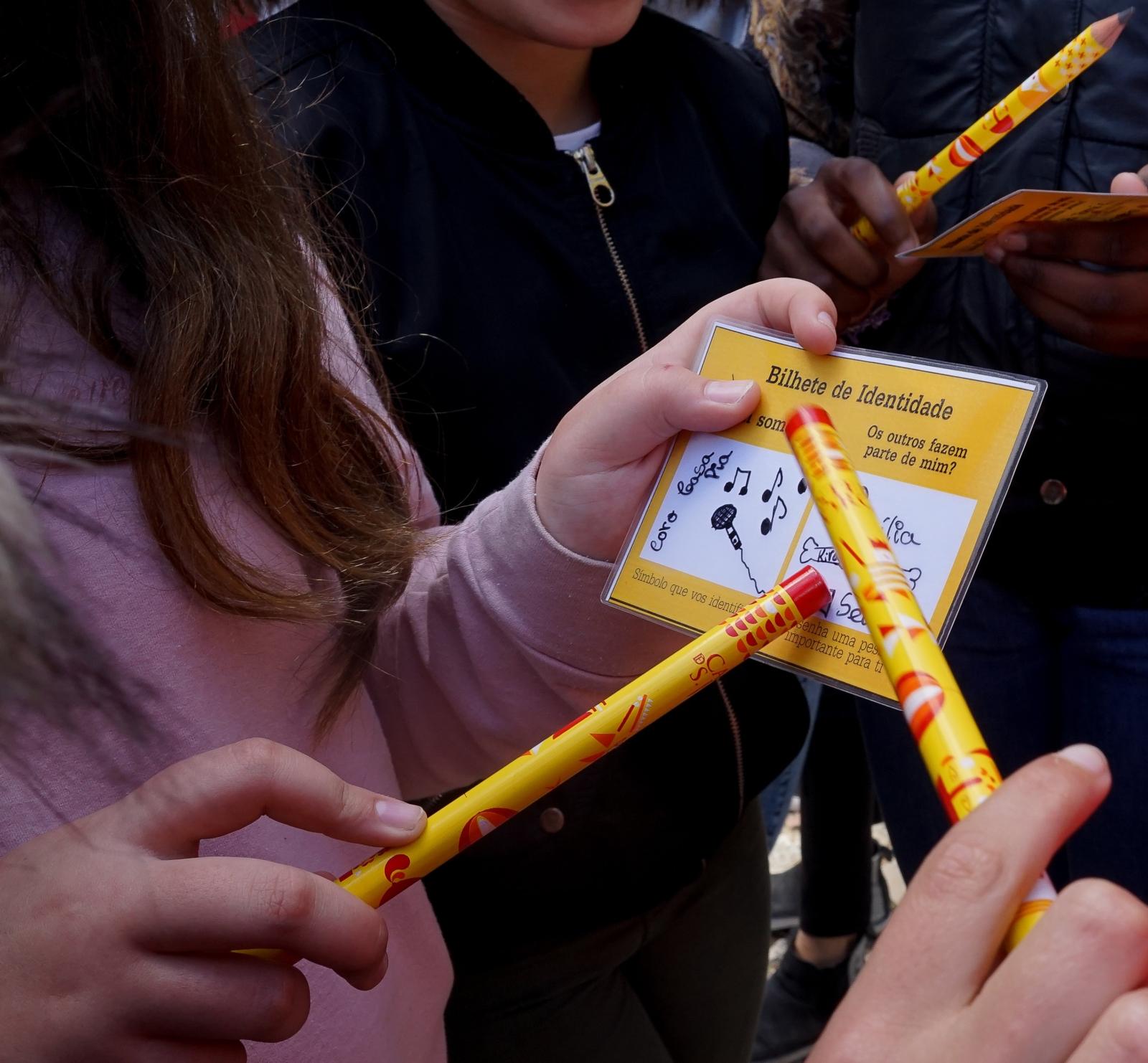 Criança a segurara cartão e lápis durante uma atividade