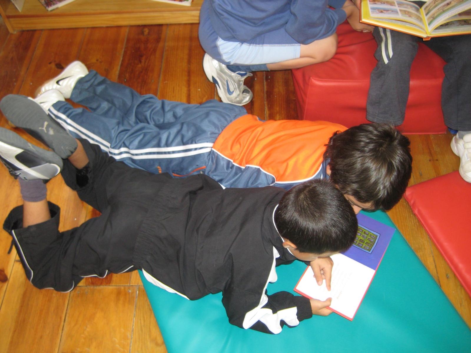Duas crianças deitadas a ler