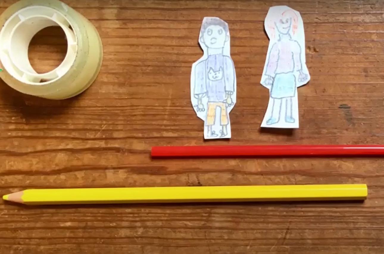 Dois lápis, uma fita cola e dois bonecos desenhados