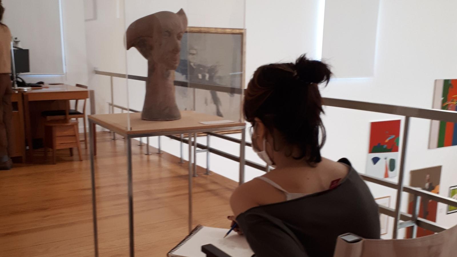 Rapariga a observar o busto de uma estátua