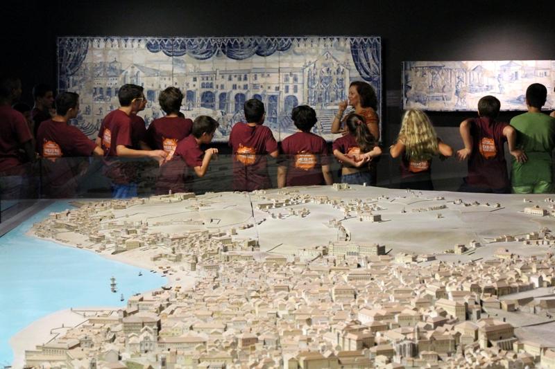 Grupo de crianças num museu a ver um painel de azulejos alusivo a Lisboa antiga