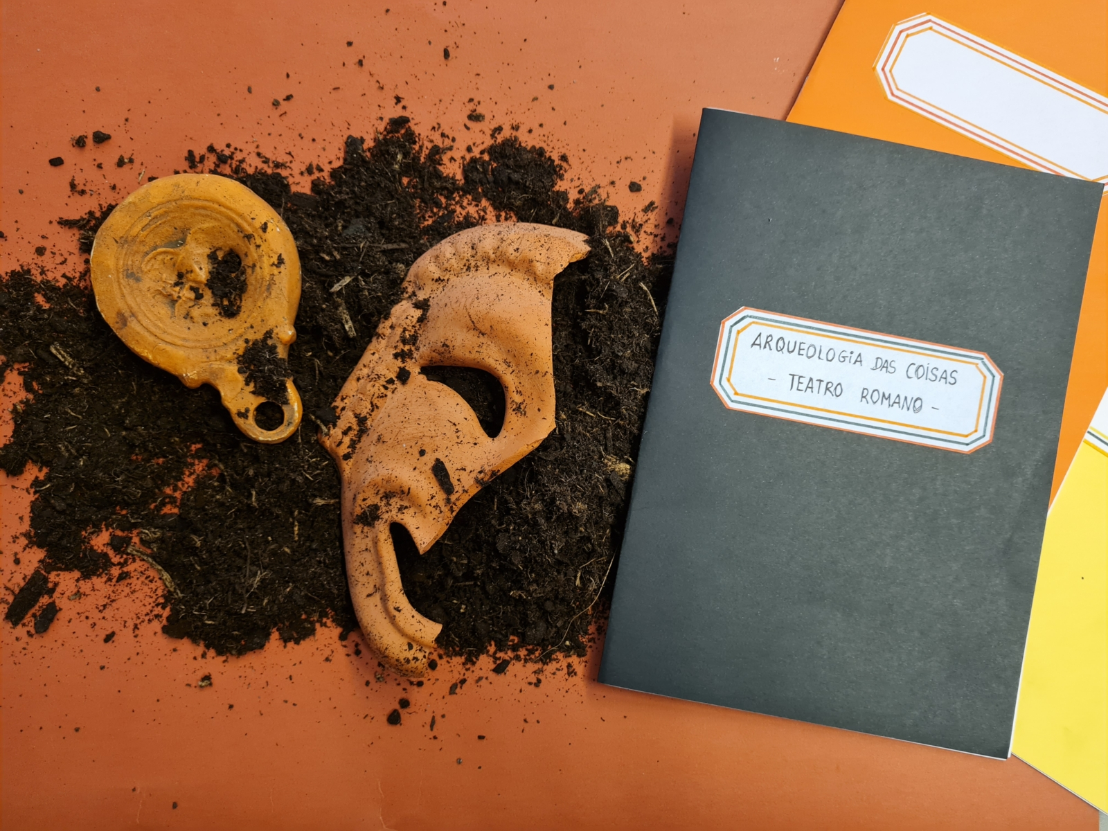 dois cadernos, uma máscara em barro partida em cima de um punhado de terra