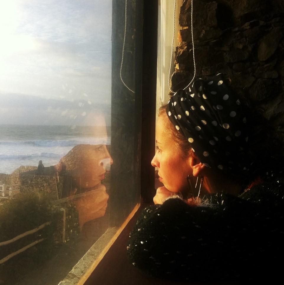 Mulher olha a paisagem pela janela