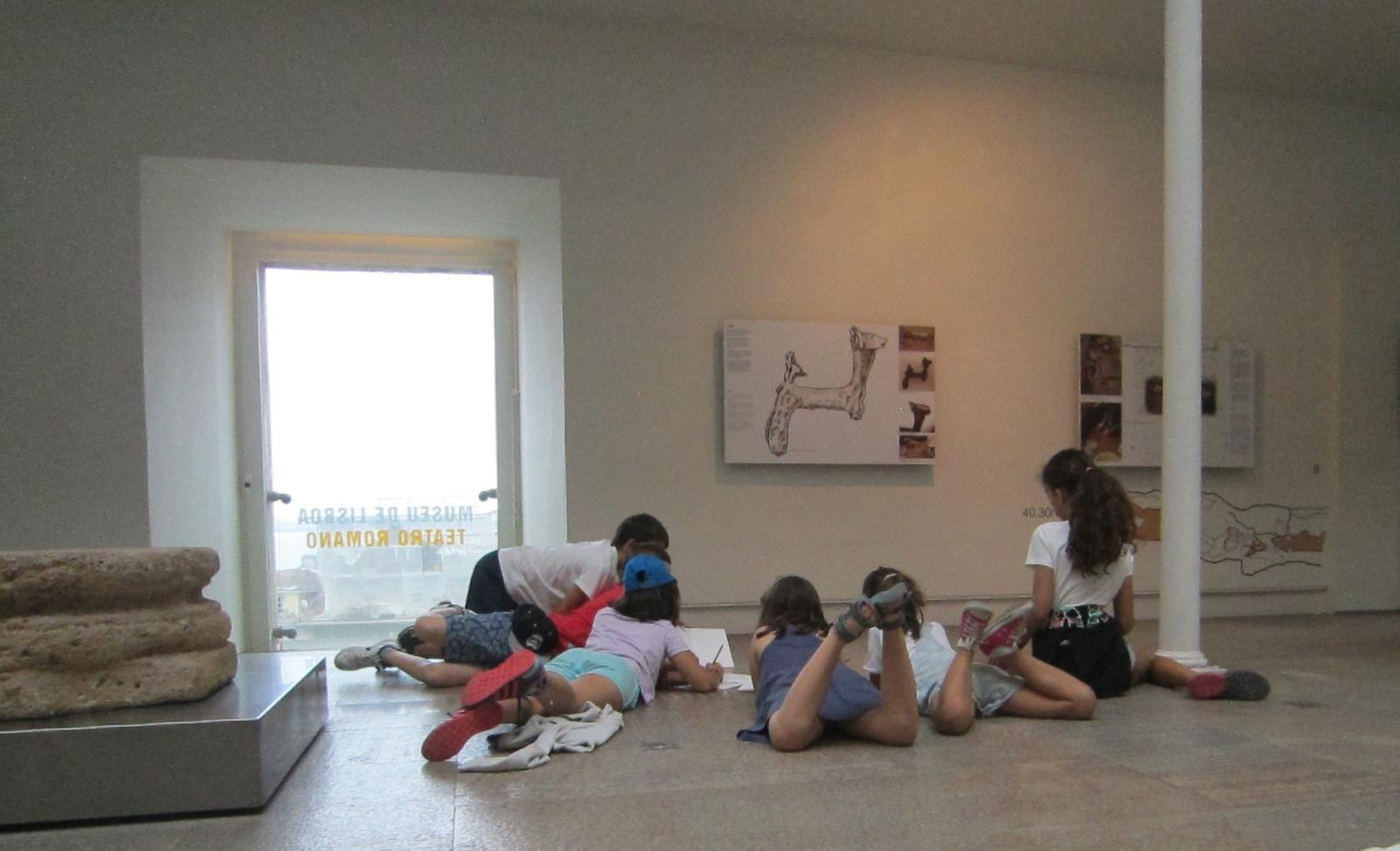 Crianças a desenhar no chão de uma galeria em frente a um quadro