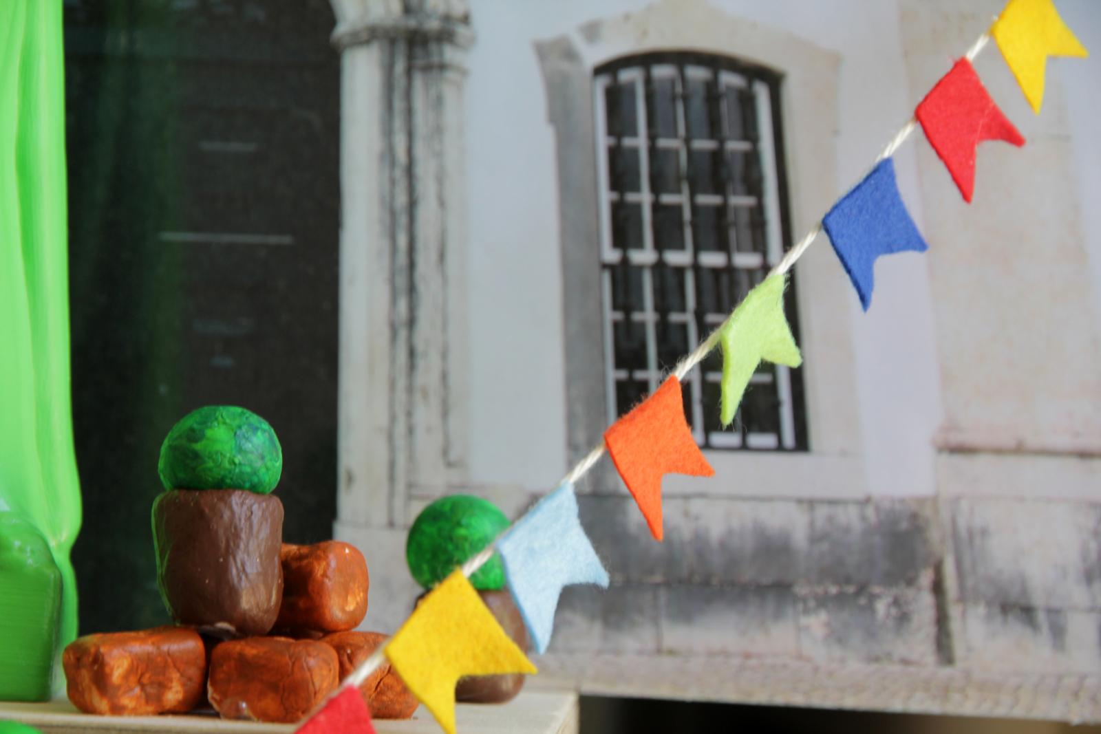 Banca com majericos artificiais e fita alusiva a arraial