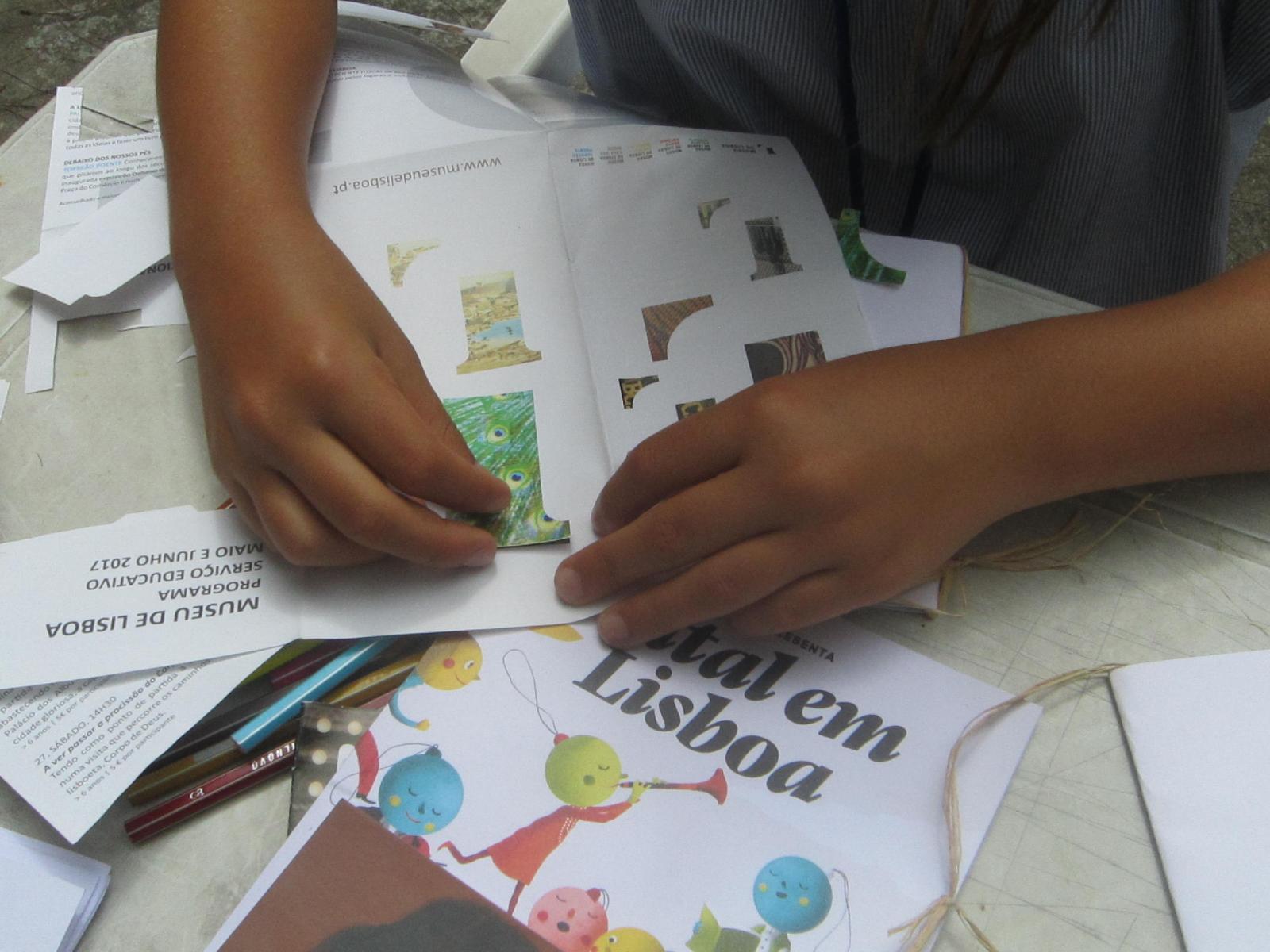 Mãos de uma criança a fazer colagens em papel