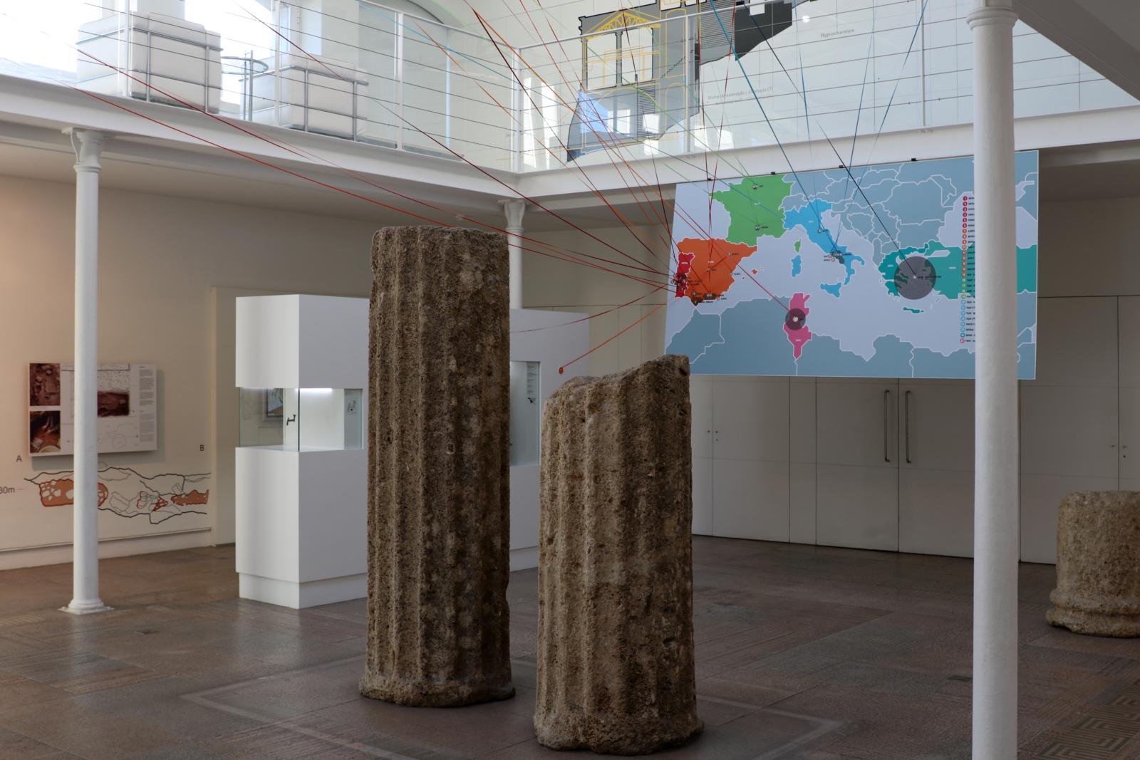 Espaço expositivo, com duas colunas romanas partidas, e um mapa do mundo