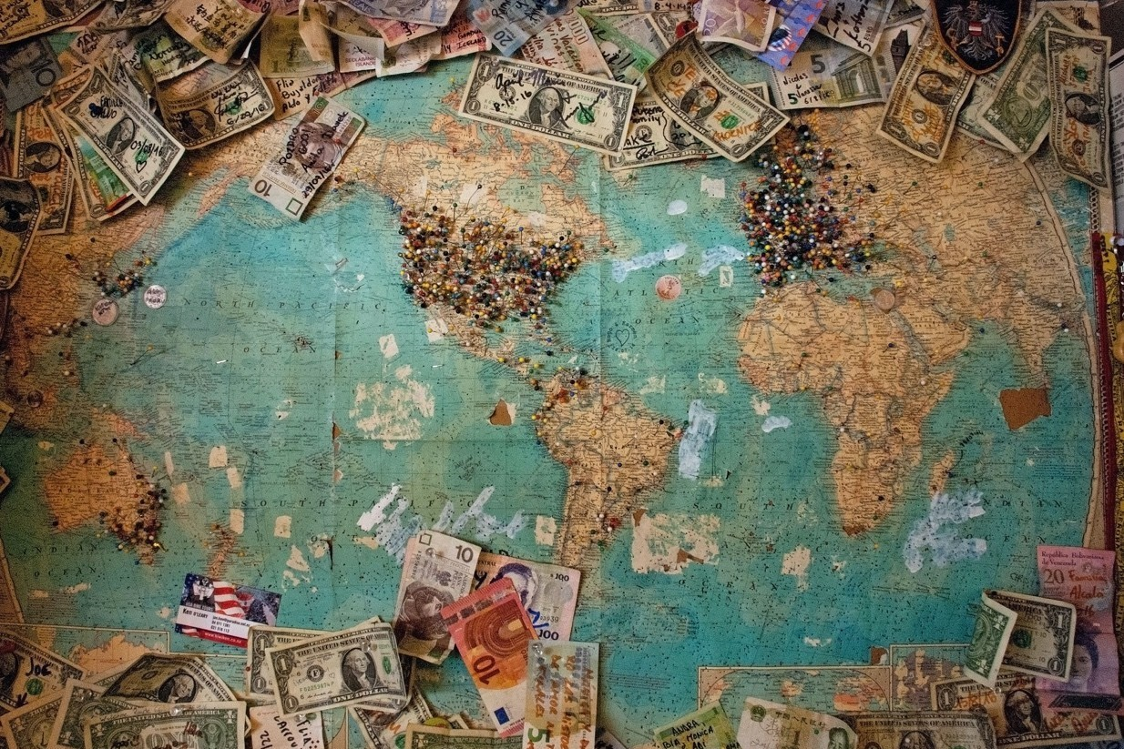 Mapa mundo, com várias notas de dinheiro espalhadas em cima deste