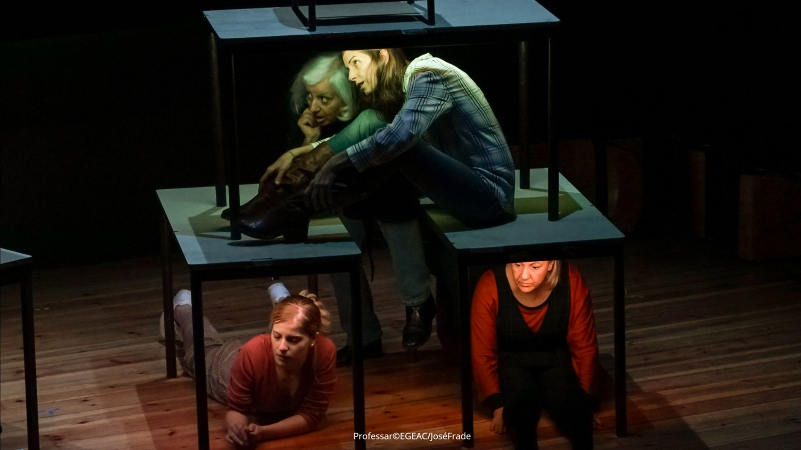 Quatro mulheres em palco, em performance, em cima e debaixo de mesas