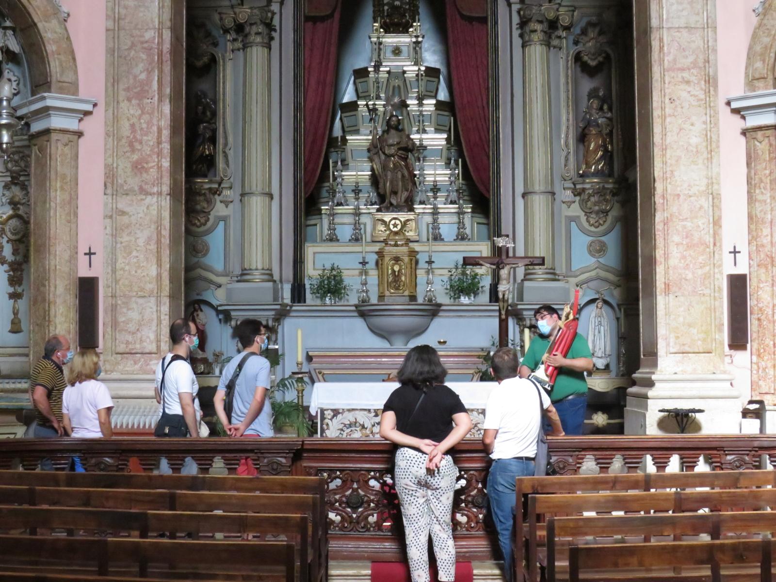 Pessoas a observar um altar de uma igreja