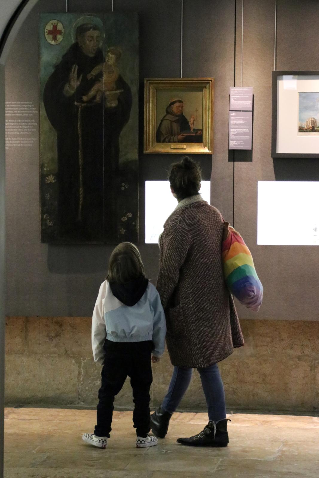 Mãe e filho no Museu a olhar para duas pinturas representativas de Santo António