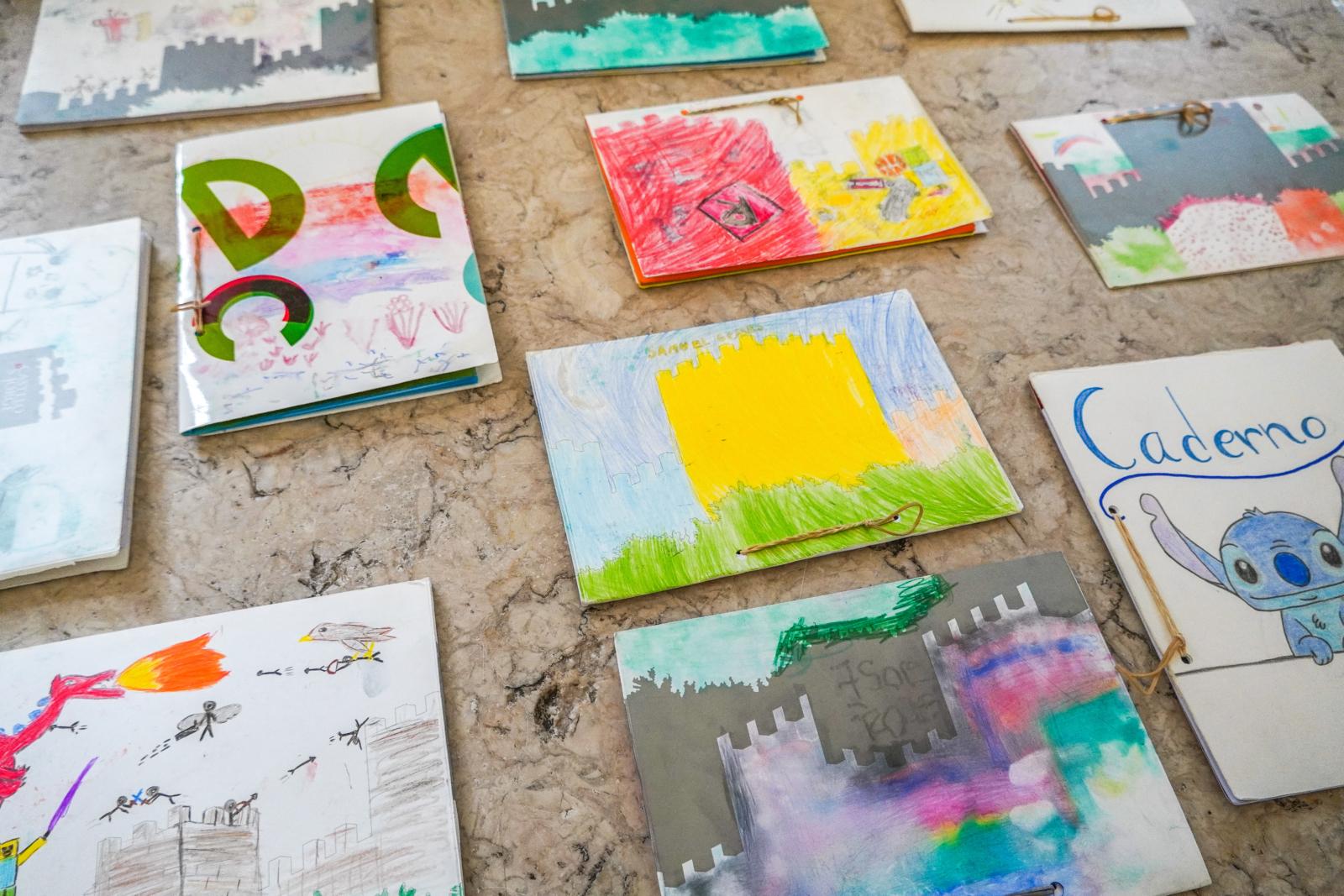 Vários cadernos com as capas ilustradas por crianças
