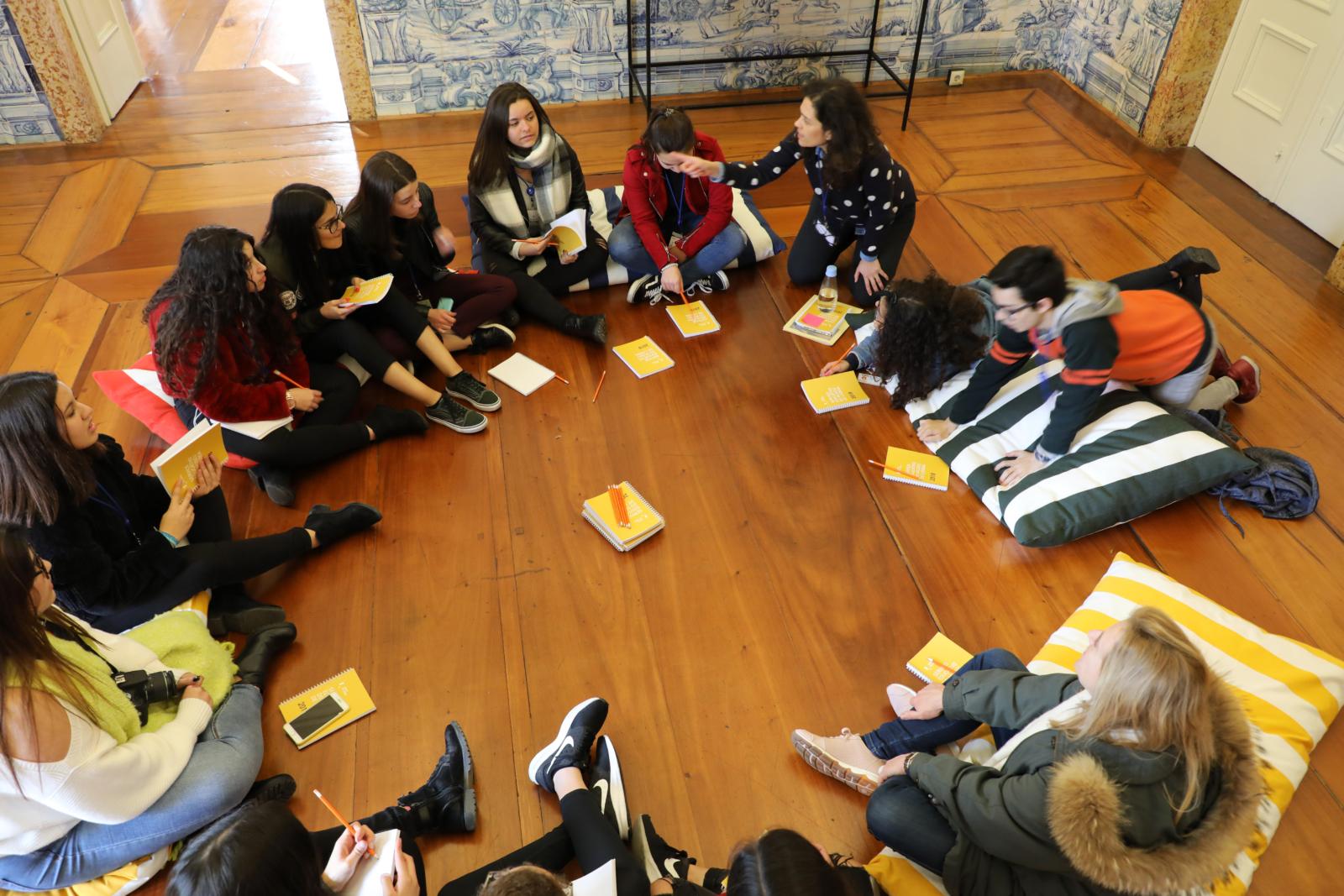 Crianças sentadas em circulo no chão, com as mediadoras a realizar uma atividade