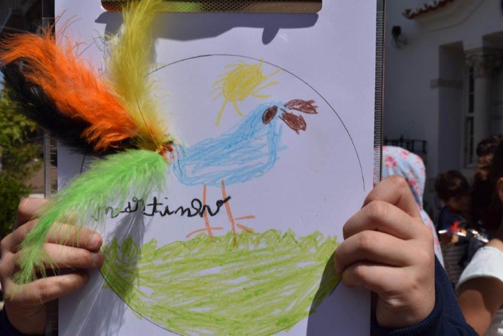 Criança a mostrar desenho e colagens