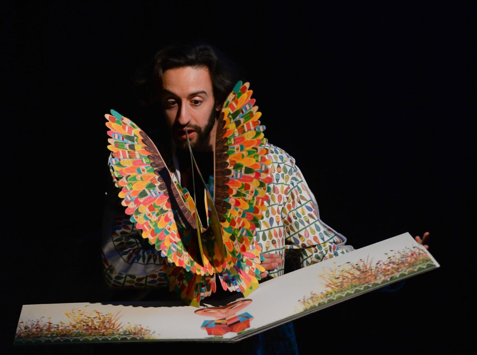 Artista em cena com um livro ilustrado e um pássaro de muitas cores em papel