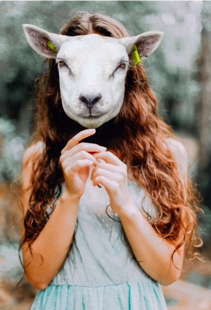 Mulher a segurar máscara de animal à frente da sua própria cara
