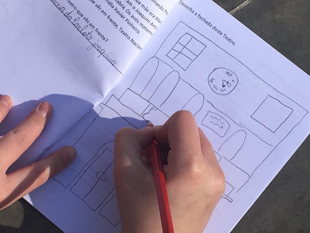 Mãos de criança a desenhar em caderno
